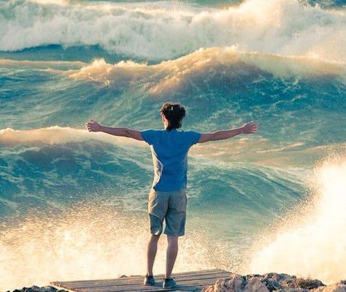 Ragazzo con le braccia aperte davanti all'oceano - Danza nel flusso
